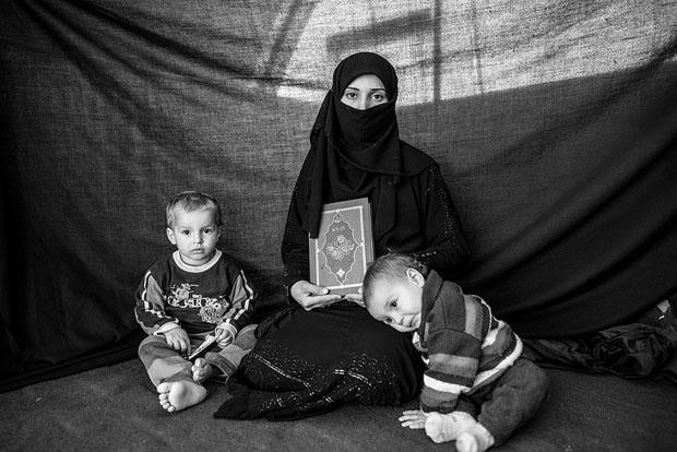 """Iman, de 25 años, en el campo de refugiados de Nizip, en Turquía. Cuando huyó de Alepo lo único que llevó consigo fueron sus hijos, Ahmed y Aisha, y un Corán: """"Mientras lo tenga junto a mí, me sentiré conectada con Dios"""". Foto: Brian Sokol / UNHCR"""
